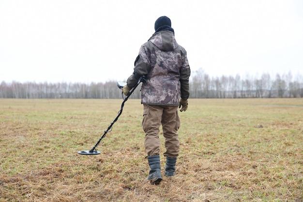 Cacciatore di tesori con un metal detector nel campo