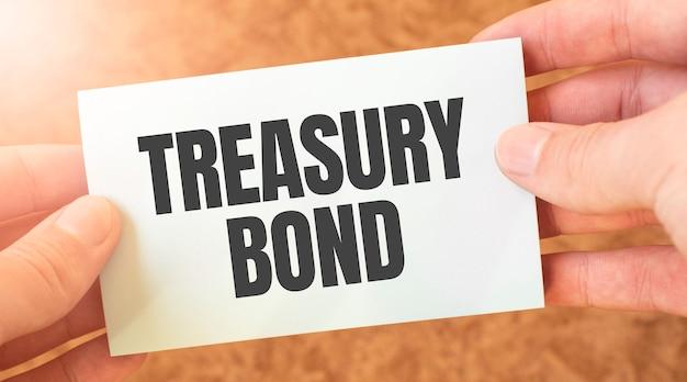 Iscrizione di parola di buoni del tesoro sul foglio di carta della carta bianca nelle mani di un uomo d'affari