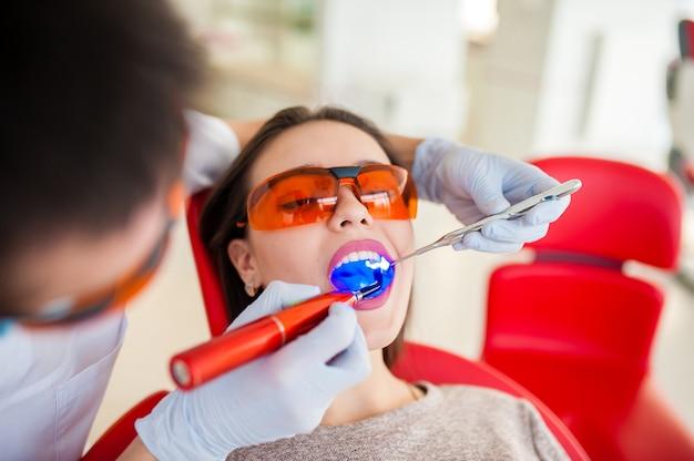 Trattamento della bella ragazza di tenuta leggera in odontoiatria.