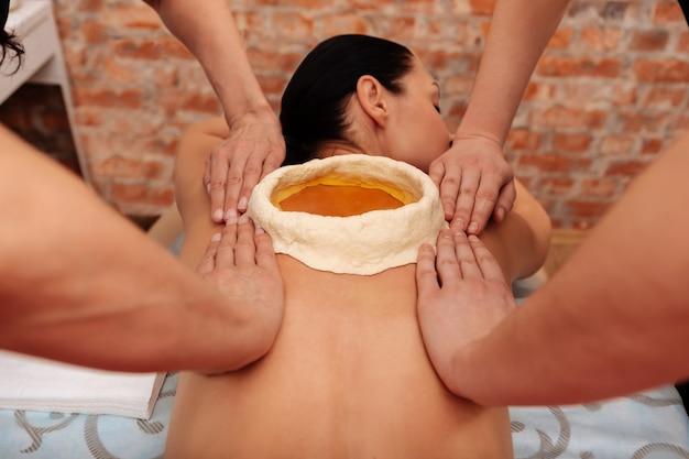 Trattamento in salone. donna dai capelli scuri rilassata che riceve una procedura scomoda insolita e maestri appoggiati sulla schiena