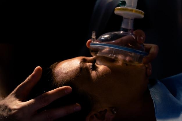 Trattamento di una forma grave di coronovirus covid-19. il medico indossa una maschera per la ventilazione artificiale dei polmoni nell'unità di terapia intensiva