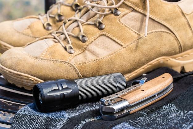 Attrezzatura da trekking o da trekking: scarponi, calze, coltello pieghevole e torcia. foto d'archivio