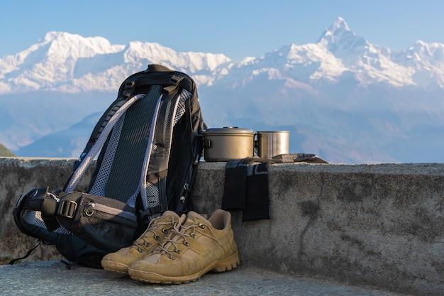 Trekking o attrezzatura da trekking con la catena montuosa dell'annapurna sullo sfondo. zaino, scarpe da trekking, calzini, tazza di metallo e bollitore. concetto di attività all'aperto.