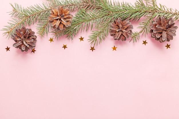 Un ramo di un albero con coni su sfondo rosa, celebrazioni di natale e capodanno