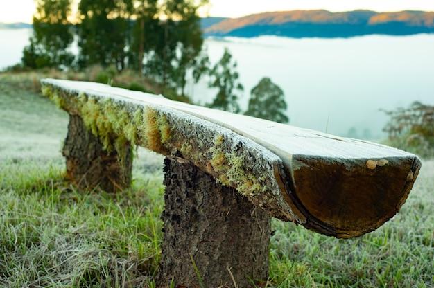 Panchina in tronchi d'albero gelata dal gelo sui monti urubici