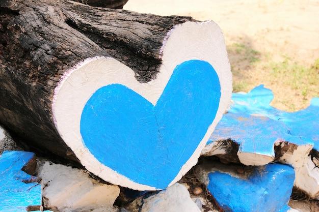 Il tronco dell'albero ha la forma di un cuore, dipinto con vernice blu e bianca. un cuore blu è dipinto su un tronco d'albero segato. concetto di amore.