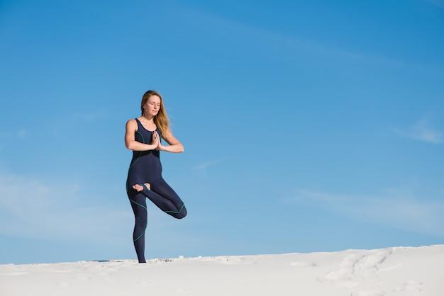 Posa di yoga dell'albero dalla giovane donna in deserto