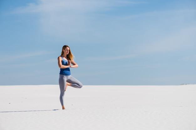 Posa di yoga dell'albero nel deserto bianco