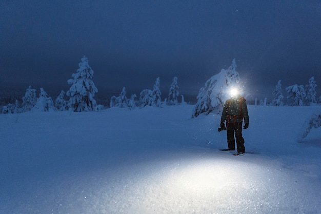 Trekker con una lampada frontale che cammina in un innevato parco nazionale di riisitunturi, finlandia