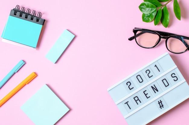Trend concept 2021, scatola luminosa con iscrizione, dischi per quaderno, penne, fiore.