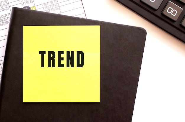 Testo trend su un adesivo sul desktop. diario e calcolatrice. concetto finanziario.