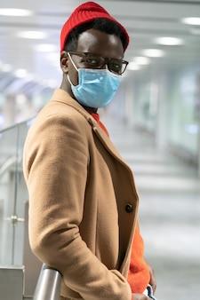 Uomo alla moda hipster africano che guarda l'obbiettivo, in piedi nel terminal dell'aeroporto, indossare la maschera. covid-19