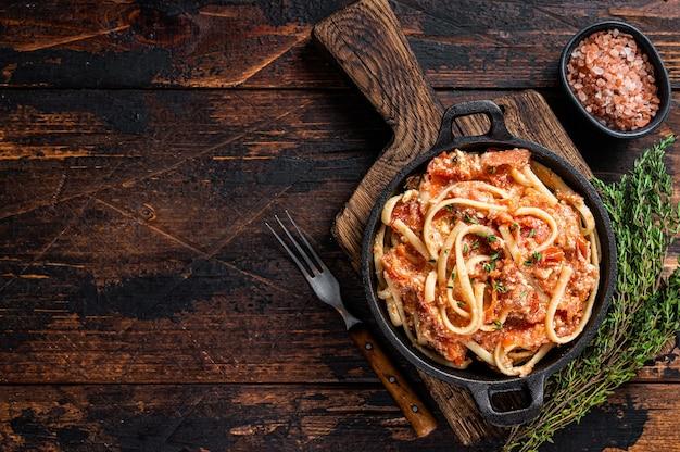 Feta al forno alla moda con pomodori al forno e formaggio in padella. fondo in legno scuro. vista dall'alto. copia spazio.