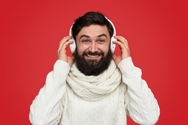Uomo barbuto alla moda in sciarpa che ascolta la musica