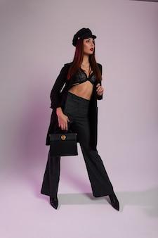 Bella giovane donna alla moda con labbra rosse sexy in berretto alla moda nero in reggiseno in cappotto lungo in pantaloni in stivali con una borsa è in piedi in una stanza vicino al muro. elegante modello di moda ragazza moderna al chiuso.
