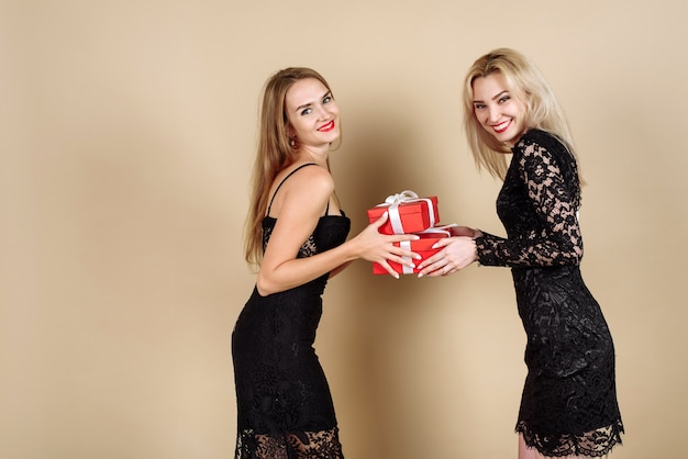 Signora bionda d'avanguardia in vestito luminoso nero che dà regalo alla sua ragazza con la scatola