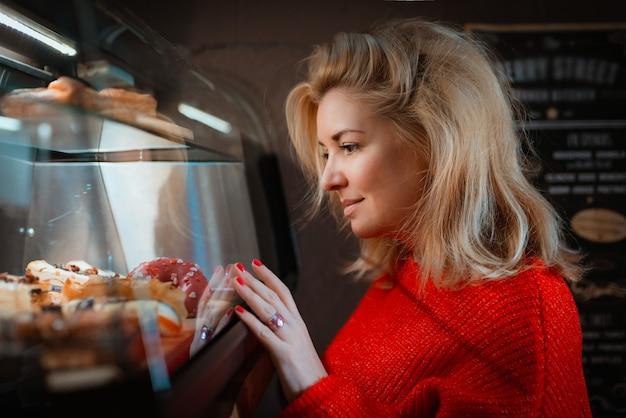 Donna bionda alla moda in maglione rosso dalla finestra del negozio di ciambelle dolci.