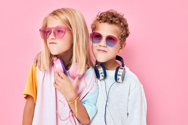 Ragazzo e ragazza alla moda con gli occhiali da sole si divertono con la moda casual per bambini di amici