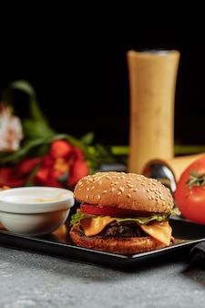 Hamburger alla moda con pollo in panino nero con ingredienti e patatine fritte su legno vintage disordinato