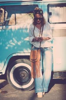 Donna caucasica alla moda di 40 anni con cellulare - tendenza della moda gente felice all'aperto che si gode lo stile di vita - alternativa alle vacanze di viaggio