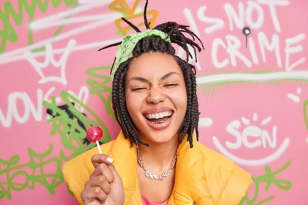 La ragazza alla moda hipster allegra sorride ampiamente detiene il lecca-lecca si diverte con gli adolescenti della stessa età indossa pose di gilet giallo contro il muro di graffiti colorati