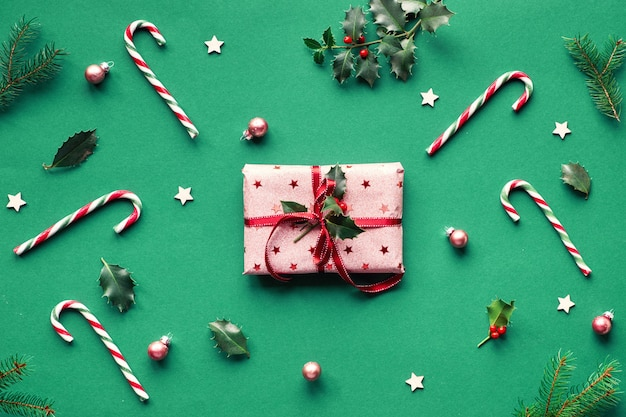 Piatto alla moda di natale giaceva su sfondo di carta verde con bastoncini di zucchero, ramoscelli di agrifoglio e abete, stelle di legno e ninnoli. confezione regalo avvolta in carta da regalo rosa con nastro rosso e ramoscello di agrifoglio naturale.