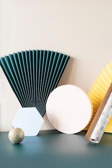 Composizione alla moda di forme geometriche beige e bianche, ventagli di carta verde smeraldo e giallo e carta da regalo natalizia e ornamento dorato su sfondo a blocchi di colore per il posizionamento del prodotto