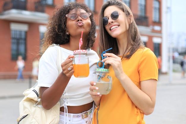 Ragazze alla moda cool hipster, amici bevono cocktail sullo sfondo urbano della città.