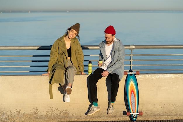 Le coppie alla moda si godono il sole al tramonto con tè e longboard su un ponte di cemento vestito con abiti da strada