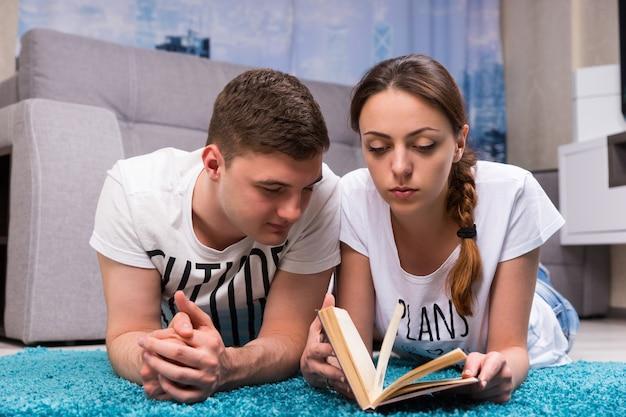 Coppia alla moda sdraiata su un tappeto nel loro soggiorno e leggendo un libro in un'atmosfera rilassata