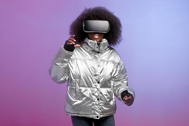 La ragazza alla moda dai capelli castani riccia vestita con una giacca color argento utilizza gli occhiali per realtà virtuale in studio su sfondo al neon.