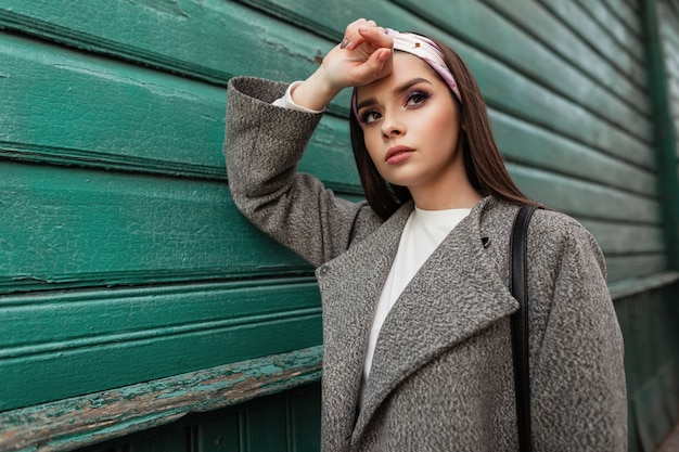 Giovane donna sveglia alla moda con bel trucco in bandana alla moda in elegante cappotto grigio resto vicino casa in legno verde vintage. la ragazza urbana abbastanza attraente affascinante cammina sulla città. look casual giovanile.