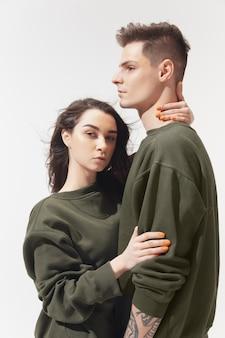 Coppia alla moda alla moda isolata sul muro bianco