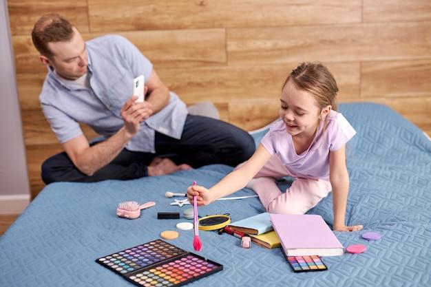 Padre alla moda scatta foto di sua figlia alla moda usando cosmetici, uomo e bambino si siedono insieme sul letto