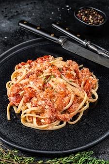 Pasta alla moda feta con pomodorini al forno e formaggio su un piatto. sfondo nero. vista dall'alto.