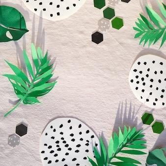 Trendy flat lay, vista dall'alto con elementi decorativi in carta, verde su sfondo bianco tessile. foglie esotiche, forme astratte maculate ed esagoni di carta.