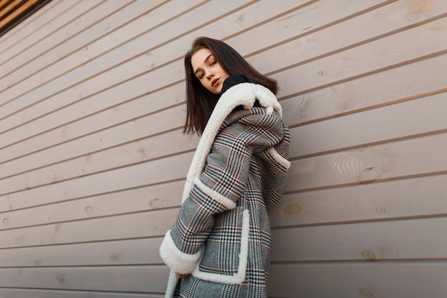 Ragazza alla moda in abiti di moda vicino a una parete in legno