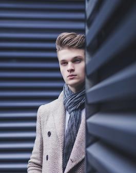 Ragazzo alla moda in cappotto e in piedi vicino a un muro metallico a new york