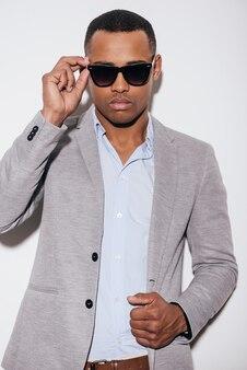 Bello alla moda. fiducioso giovane africano in occhiali da sole che si aggiusta la giacca