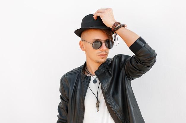 Alla moda bel giovane con cappello e occhiali da sole in una giacca elegante nera su sfondo bianco