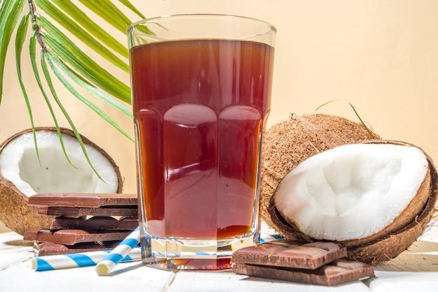 Bevanda biologica salutare alla moda. cocktail vegano fatto in casa con acqua di cocco e cioccolato, con pezzi di cioccolato, noci di cocco fresche e decorazioni di foglie di palma, spazio copia copy