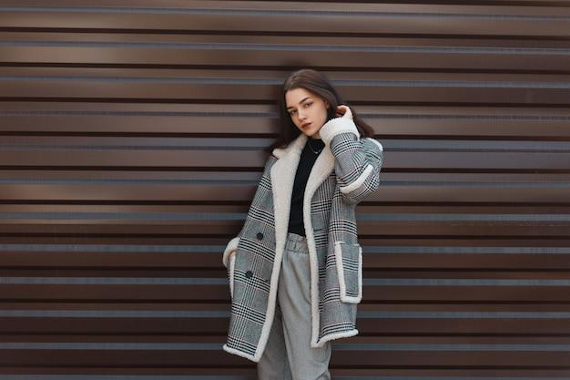 Bella ragazza alla moda in abiti di moda all'aperto