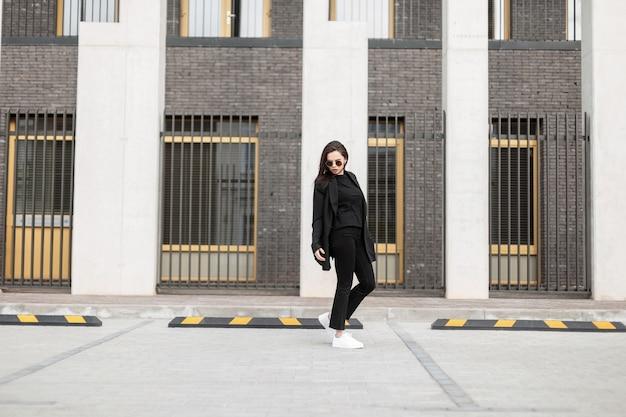 La giovane donna urbana adorabile alla moda in occhiali da sole alla moda in giacca giovanile alla moda in scarpe bianche è in piedi vicino a un edificio d'epoca in città. modello di moda bella ragazza moderna in abito casual all'aperto