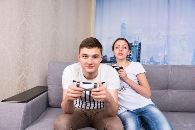 I giocatori di sesso maschile e femminile alla moda che giocano ai videogiochi seduti insieme su un divano a casa in un'atmosfera rilassata