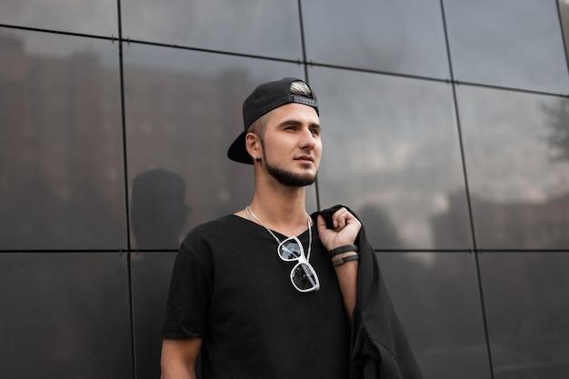 Uomo alla moda in abiti neri cammina per strada