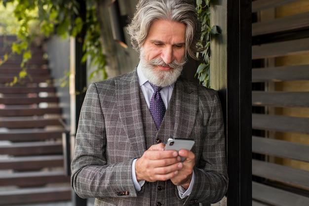 Uomo alla moda con la barba che naviga nel telefono cellulare