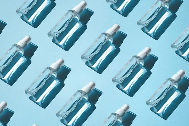 Modello alla moda di spray con antisettico alcolico, disinfettanti su sfondo blu.