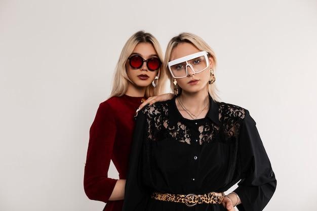 Ritratto alla moda di due ragazze adolescenti in occhiali colorati con capelli biondi in abiti rosso-neri in piedi vicino a un muro grigio vintage
