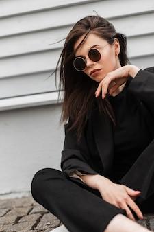 La giovane donna urbana sexy alla moda in occhiali da sole rotondi alla moda in giacca nera alla moda per giovani gode di un riposo vicino alla parete di legno dell'annata in città. modello di moda bella ragazza moderna in abbigliamento casual all'aperto.