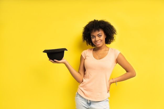 Trendy sexy giovane femmina in cappello nero che indossa abiti casual in posa su sfondo giallo